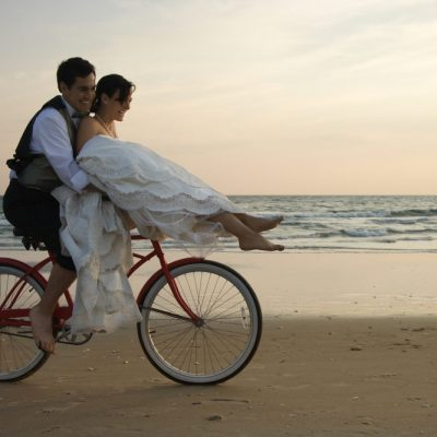 Newlyweds right a bike on the beach